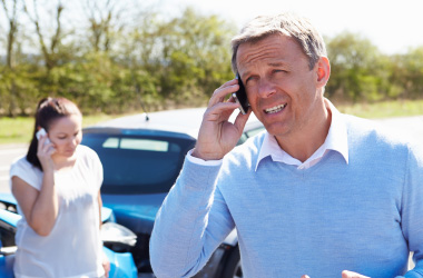 Mand and woman making a phone call after car accident